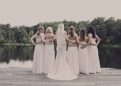 bride and bridesmaids on dock overlooking lake at Seven T Farms outdoor st louis area wedding venue in sullivan missouri
