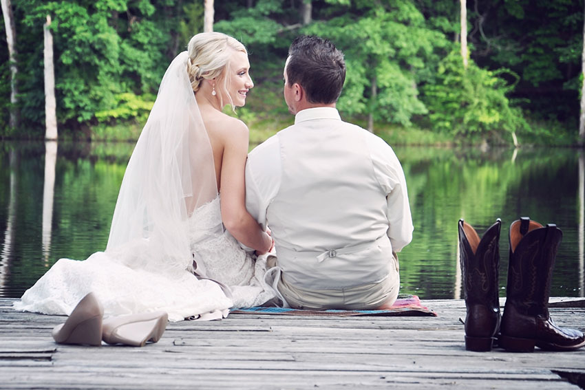 bride and groom sitting on dock at Seven T Farms Wedding venue in Sullivan Missouri