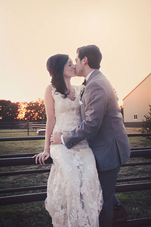 kissing couple on fence at Seven T Farms outdoor st louis area wedding venue in sullivan missouri