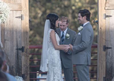 couple reciting vows with barnwood door backdrop at Seven T Farms outdoor st louis area wedding venue in sullivan missouri